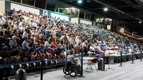 Mitglieder sitzen in der Messehalle 1 der Messe Chemnitz bei der Mitgliederversammlung des Chemnitzer FC.