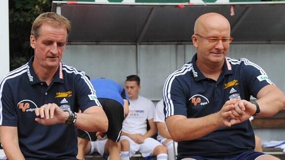Petrik Sander und Thomas Hossmang schauen 2013 auf ihre Uhren.