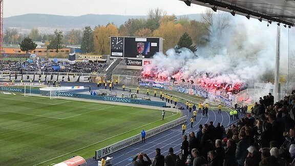 Brennende Pyrotechnik im Fanblock von Hansa Rostock beim Spiel gegen FC Carl Zeiss in Jena