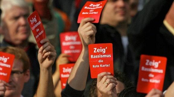 Menschen halten rote Karten in die Höhe