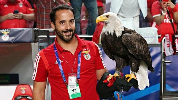 Der Benfica Adler, çguias sitzt auf dem Arm eines Mannes.