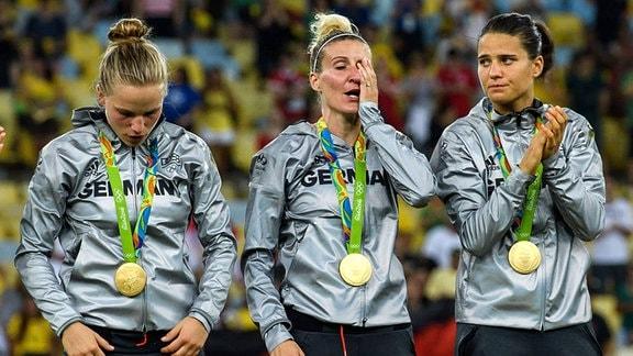 Deutschland ist Olympiasieger - Dzsenifer Marozsan, Anja Mittag und Tabea Kemme stehen sichtlich bewegt auf dem Treppchen. 2016