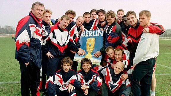 Coach Eduard Geyer und seine Spieler, u.a. Toralf Konetzke, Jens Melzig, Willi Kronhardt mit einem Plakat für das DFB-Pokalfinale in Berlin, 1997