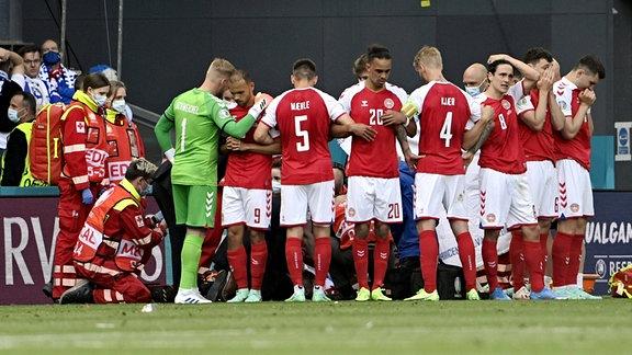 Die Fussballer der dänischen Nationalmannschaft bilden einen Kreis um Christian Eriksen, der medizinisch behandelt wird.
