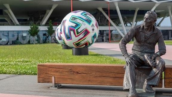 Eine Plastik des Firmengründers Adi Dassler auf dem Gelände der Firmenzentrale mit großen, offiziellen Spielbällen, die im ganzen Stadtgebiet von Herzogenaurach zu finden sind.