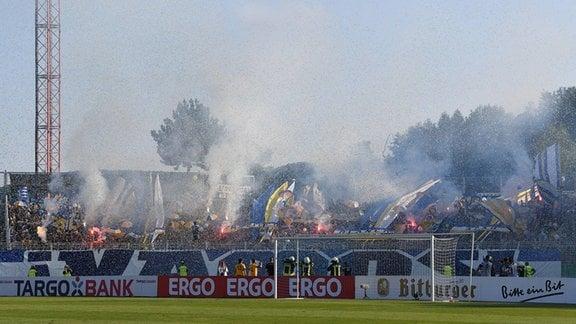 Fans aus Jena in der Südkurve brennen Feuerwerk ab.