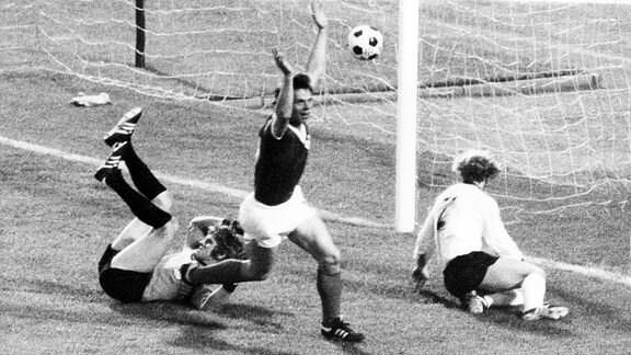 DDR-Stürmer Jürgen Sparwasser (M) von der jubelt am 22.06.1974 im Hamburger Volksparkstadion nach seinem Treffer zum 1:0 gegen die Bundesrepublik Deutschland mit erhobenen Armen, der geschlagene westdeutsche Torhüter Sepp Maier (l) und Verteidiger Berti Vogts (r) sind konsterniert.