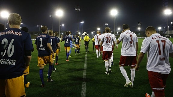 Zwei Fußballmannschaften betreten ein Spielfeld