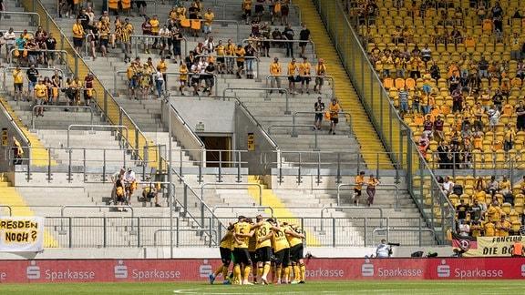 Mannschaftskreis vor dem Spiel. Im Hintergrund stehen Fans im K-Block mit Abstand.