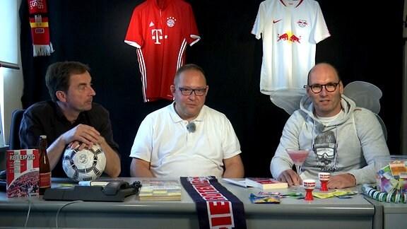 Drei Männer sitzen an einem Tisch. Im Hintergrund zwei Fußballtrikots. Das eine ist rot und gehört zum Verein FC Bayern München. Das andere ist weiß und gehört zum Verein RB Leipzig