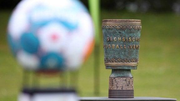 Der neue Sachsenpokal steht vor einem Fußball