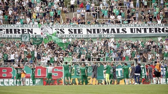Die Mannschaft von BSG Chemie Leipzig feiert mit Fans