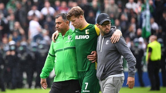 Alexander Bury BSG Chemie Leipzig kann nach seiner Behandlung mit Hilfe von Betreuern das Spielfeld verlassen