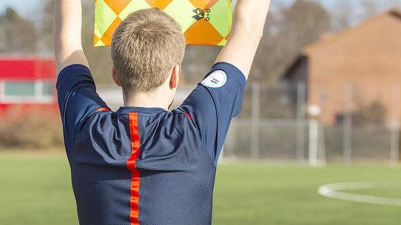 Ein Schiedsrichter zeigt dem Hauptschiedsrichter den Wechselwunsch einer Mannschaft an.