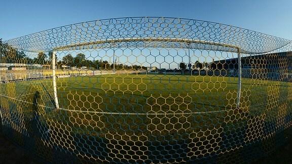 Blick ins Bruno-Plache-Stadion (1. FC Lok Leipzig) in Hintertoransicht und einem Tornetz in blau-gelb mit Flutlichtmasten und Haupttribüne