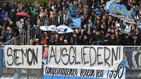 Chemnitzer Fans haben Plakate im Gästeblock aufgehängt Darauf steht ''Siemon ausgliedern''.