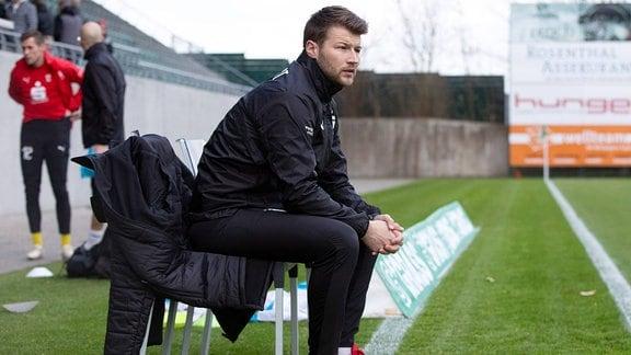 Trainer Daniel Berlinski sitzt am Spielfeldrand.