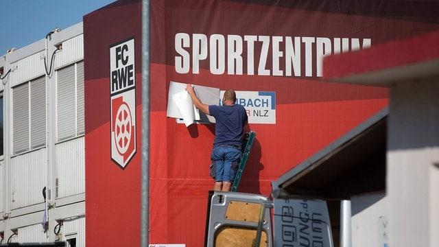 Die Werbung von Rolf Rombach wird am Nachwuchsleistungszentrum NLZ überklebt.