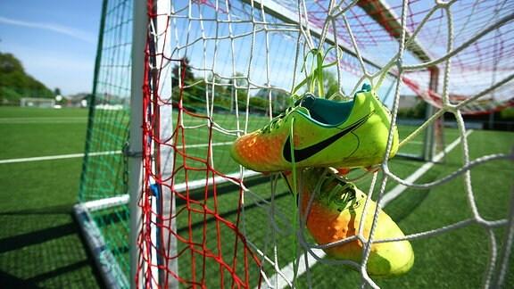 Fußballschuhe hängen in einem Tornetz