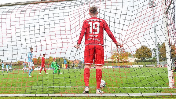 Niclas Knoop Innenverteidiger Halberstadt, Rueckennummer 19, in Rückenansicht beim Regionalliga-Spiel Halberstadt vs. Viktoria Berlin. Er hält sich am Tornetz enttäuscht nach einem Gegentor fest.