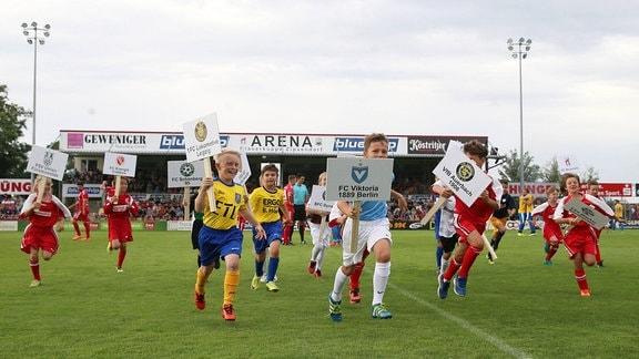 Kinder in Fußball-Trikots rennen mit Plakaten, auf denen Logos und Namen verschiedener Vereine abgebildet sind, über ein Fußballfeld.