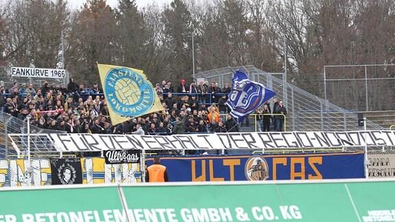 Fans im Fanblock mit Fahnen und Transparenten für den Erhalt der Regionalliga Nordost