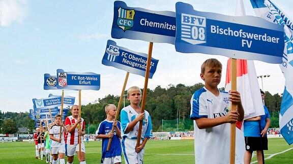 Kinder mit Schildern und Trikots der teilnehmenden Vereine in der Regionalliga Nordost