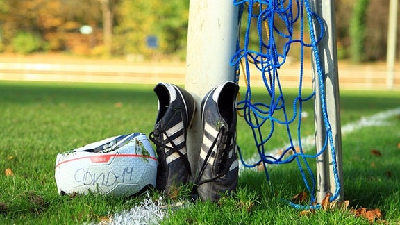 Platter Fußball und hochgestellte Schuhe neben einem Fußballtor