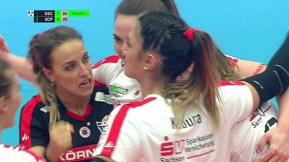 Mannschaftsfrauen freuen sich auf dem Spielfeld.