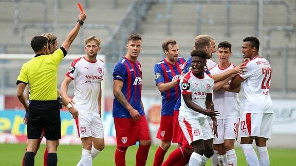 vorne 3.v.r. Braydon Manu (Hallescher FC) sieht von links, Asmir Osmanagic (Schiedsrichter) die rote Karte