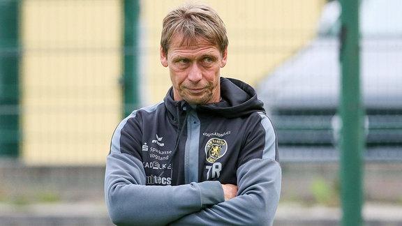 Sven Köhler steht am Spielfeldrand beim Spiel VfB Auerbach gegen Chemnitzer FC und blickt skeptisch.