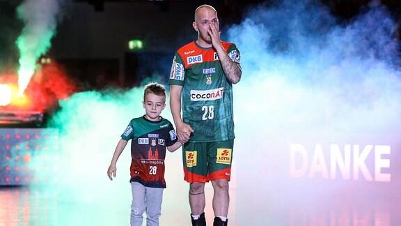 Robert Weber (SC Magdeburg) kommt mit seinem Sohn Lio und hat Tränen in den Augen