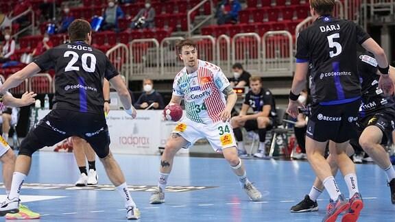 Michael Damgaard SC Magdeburg 34, im Zweikampf gegen Max Darj BHC.