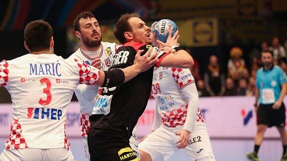 Drei Handballer während des Spiels.