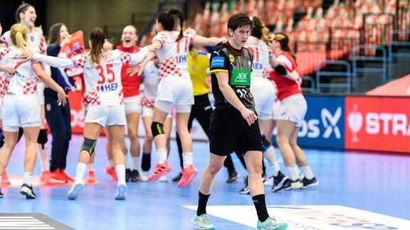 Ina Grossmann schaut niedergeschlagen, jubelnde Spielerinnen im Hintergrund