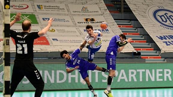 Gabriel De Santis, EHV Aue, setzt sich gegen Rauel Santos, VfL Gummersbach, und Alexander Herrmann, VfL Gummersbach, durch.