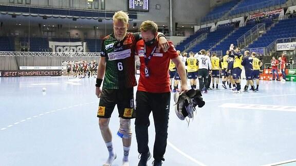 Magdeburgs Matthias Musche wird verletzt aus der Halle geführt
