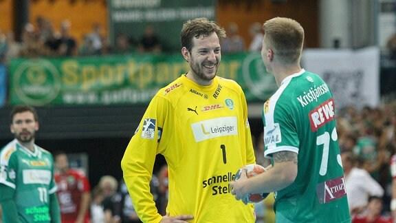 Zwei Handballspieler unterhalten sich auf dem Spielfeld.