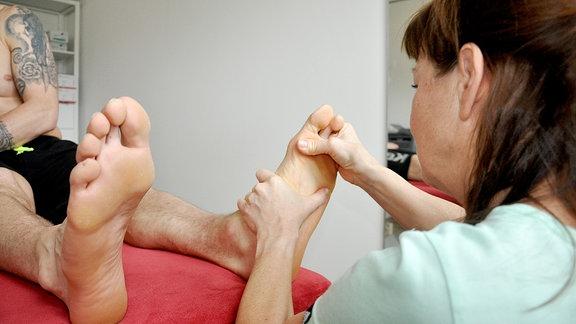 Therapeutin behandelt Füße des Patienten.