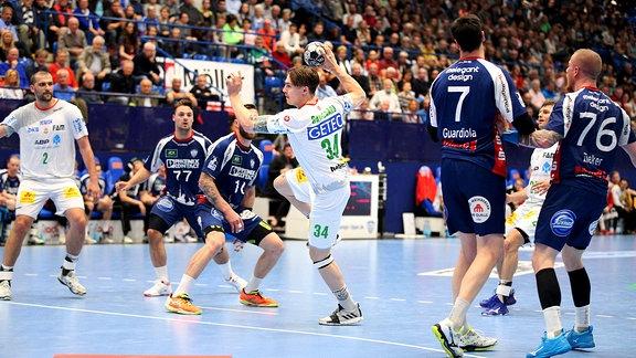 Michael Damgaard (SC Magdeburg 34) vorbei an Fabian van Olphen (TBV Lemgo Lippe 10) und Isaias Guardiola.
