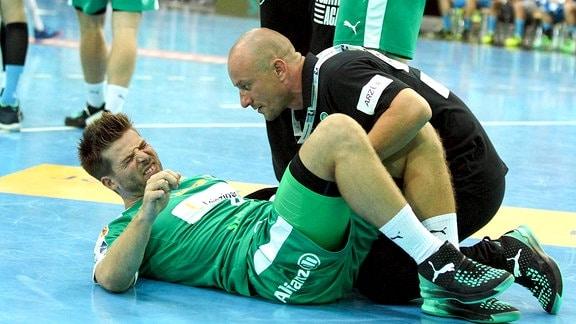 Patrick Wiesmach ( 4, DHfK) liegt verletzt am Boden.