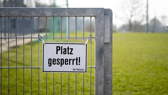 An einem Zaun haengt ein Platz gesperrt! -Schild.