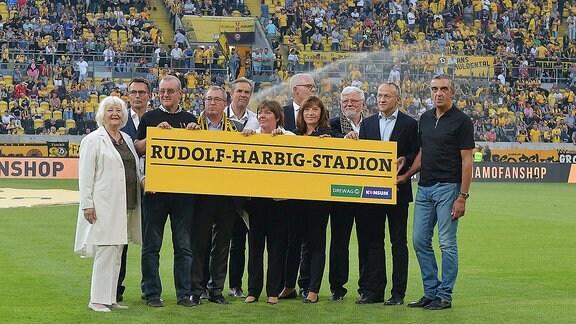 Menschen halten im Rudolf-Harbig-Stadion den Stadionnamen auf einem Schild hoch.