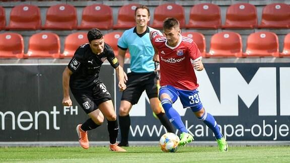 Niklas Landgraf (Hallescher FC, HFC, 31) und Christoph Ehlich (Unterhaching, 33) im Zweikampf.