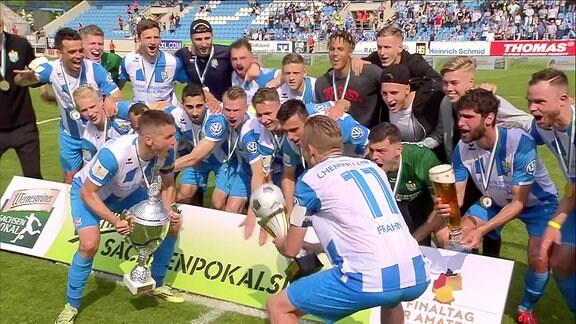 Jubelnde Spieler des Chemnitzer FC mit Meistertrophäe und Landespokal.