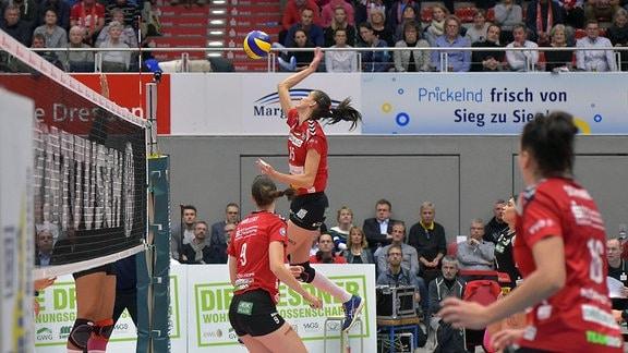 Volleyballspiel. Eine Spielerin springt zum Ball hoch.