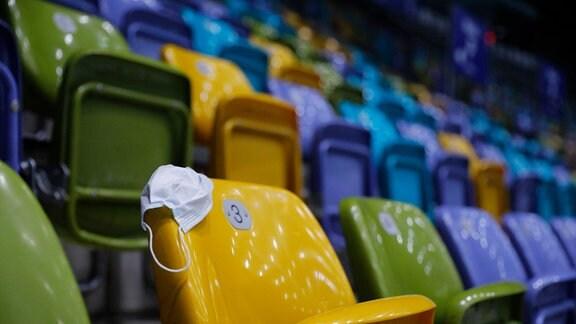 leere hochgeklappte Sitze und eine Maske United Volleys