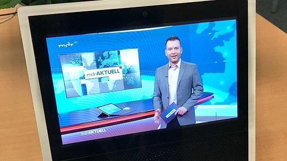 Tablet steht auf einem Tisch vor einer Zimmerpflanze. Auf dem Bildschirm moderiert ein Mann Nachrichten.