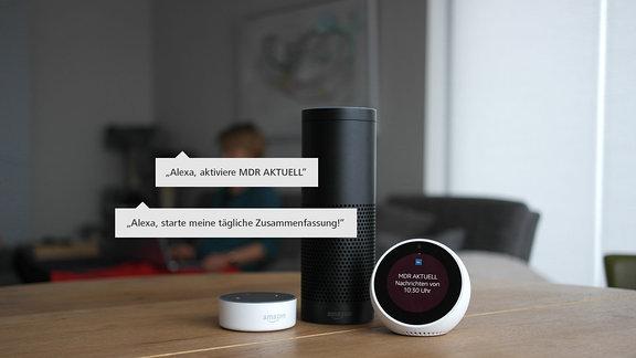 Ein schwarzes Echo 1 Gerät steht zwischen einem weißen Echo Spot rechts und einem weißen Echo Dot 2 links auf einem Tisch in einem Wohnzimmer. Auf dem Bildschirm des Echo Spot ist das Logo von MDR AKTUELL zu sehen.