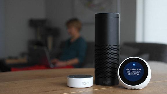 Ein schwarzes Echo 1 Gerät neben einem weißen Echo Spot und einem weißen Echo Dot 2 und von Amazon steht auf einem Tisch in einem Wohnzimmer. Auf dem Bildschirm des Echo Spot ist das Logo von MDR THÜRINGEN Das Radio zu sehen.